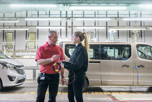 Female apprentice engineer with mentor on production line in car factoryの写真素材 [FYI03575226]
