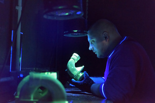 Worker using ultra-violet light to test for cracks in components in precision casting factoryの写真素材 [FYI03575277]