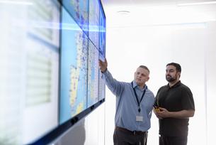 Operators in automotive emergency response control room in car factoryの写真素材 [FYI03575344]