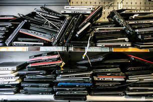 Pile of old, discarded laptops on shelfの写真素材 [FYI03575487]