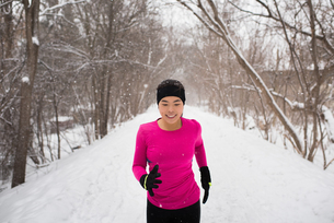 Happy young female runner in knit hat running in snow covered tree lined parkの写真素材 [FYI03575504]