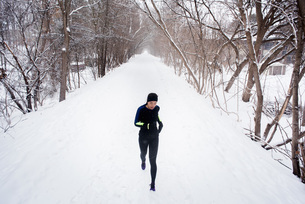 Young female runner in knit hat running in snow covered tree lined parkの写真素材 [FYI03575505]