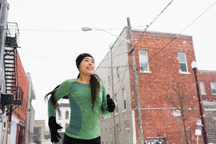 Happy young female runner in knit hat running in snowy streetの写真素材 [FYI03575506]