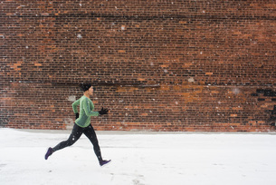 Young female runner in knit hat running along snow covered sidewalkの写真素材 [FYI03575508]
