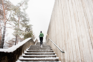 Rear view of young female runner in knit hat running up snow covered stairwayの写真素材 [FYI03575511]