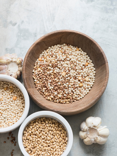 Different types of grains in bowls, garlic bulbs beside bowls, overhead viewの写真素材 [FYI03575518]