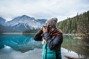 Woman taking photograph of view, Emerald Lake, Yoho National Park, Field, British Columbia, Canadaの写真素材 [FYI03575567]