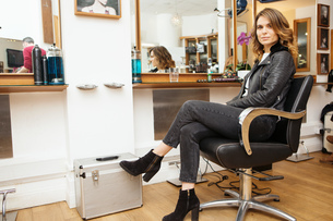 Portrait of female customer with styled brunette hair in hair salonの写真素材 [FYI03575607]