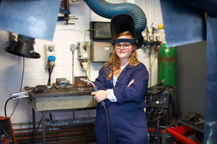 Portrait of female higher education student holding welding torch in workshop at collegeの写真素材 [FYI03575692]