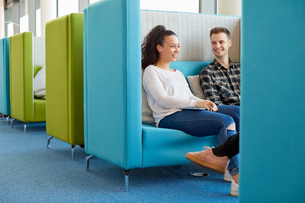 University students relaxing in modern cubicle seating areaの写真素材 [FYI03575781]