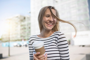 Young woman with blond flyaway hair with takeaway coffeeの写真素材 [FYI03575853]