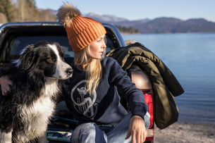Young woman and dog looking out from pick up on lakeside in Bavarian Alpsの写真素材 [FYI03575877]