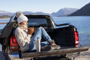 Woman with coffee sitting on pick up at lakeside in Bavarian Alpsの写真素材 [FYI03575879]