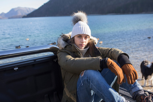Portrait of woman sitting on pick up at lakeside in Bavarian Alpsの写真素材 [FYI03575880]
