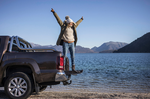 Woman with arms open standing on pick up at lakeside in Bavarian Alpsの写真素材 [FYI03575881]