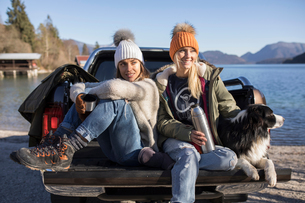Two women with coffee and dog sitting on pick up at lakeside in Bavarian Alpsの写真素材 [FYI03575882]