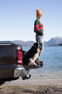 Young woman and dog standing on pick up at lakeside in Bavarian Alpsの写真素材 [FYI03575883]