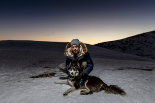 Portrait of mature man crouching with dog in snow at nightの写真素材 [FYI03575914]