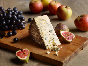 Still life of Stilton on chopping board with figs, apples and grapesの写真素材 [FYI03575952]