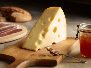 Still life of Edam cheese with quince chutney, on chopping boardの写真素材 [FYI03575954]