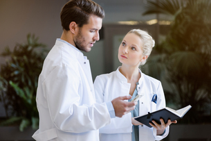 Two doctors having discussion, holding smartphone and diaryの写真素材 [FYI03575964]