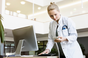 Doctor standing beside computer, holding open diary, looking at smartphoneの写真素材 [FYI03575967]