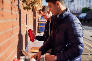 Two young men at takeaway food stand, pouring ketchup on food, Bristol, UKの写真素材 [FYI03576092]
