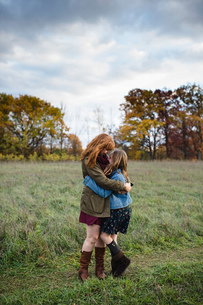 Mother and daughter hugging in meadow, Lakefield, Ontario, Canadaの写真素材 [FYI03576122]