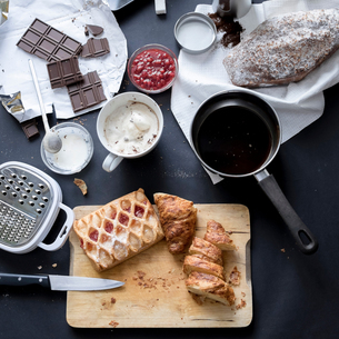 Overhead view of apple strudel, chocolate, cake and ingredients on kitchen tableの写真素材 [FYI03576170]