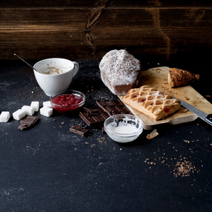 Apple strudel, chocolate, cake and ingredients on kitchen tableの写真素材 [FYI03576171]