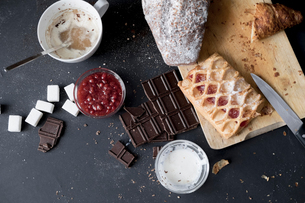 Overhead view of apple strudel, chocolate, cake and ingredients on kitchen tableの写真素材 [FYI03576175]
