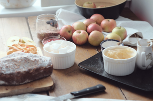 Cake and desert ingredients with apples on kitchen tableの写真素材 [FYI03576177]