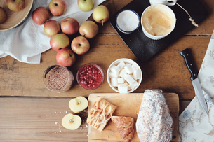 Overhead view of cake and desert ingredients with apples on kitchen tableの写真素材 [FYI03576179]