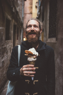 Mid adult man with gelato in dark alley, Venice, Italyの写真素材 [FYI03576262]