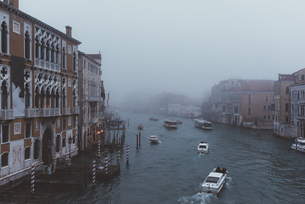 Elevated view of motor boats on misty canal, Venice, Italyの写真素材 [FYI03576281]