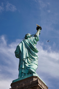 Low angle view of Statue of Liberty and airplane in blue sky, New York city, USAの写真素材 [FYI03576340]