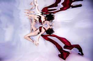 Underwater view of poised woman with wearing flowing red textilesの写真素材 [FYI03576454]