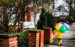 Rear view of boy in yellow anorak carrying umbrella along streetの写真素材 [FYI03576502]