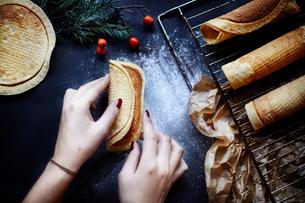 Woman making krumkake cookies, overhead viewの写真素材 [FYI03576573]