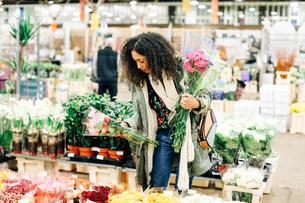 Female florist selecting flowers at new Covent Garden flower market, London, UKの写真素材 [FYI03576699]