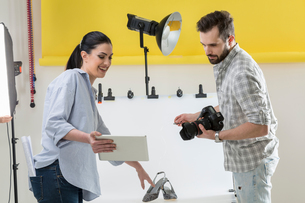 Stylist and photographer looking at digital tablet in photography studioの写真素材 [FYI03576760]