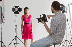 Photographer pointing at model in white backdrop photography studio shootの写真素材 [FYI03576767]