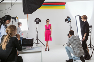 Photography team and model in white backdrop photography studio shootの写真素材 [FYI03576769]