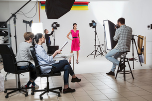 Photography team and model in white backdrop photography studio shootの写真素材 [FYI03576770]