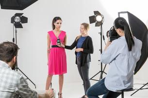 Photographer using light meter in white backdrop photography studio shootの写真素材 [FYI03576772]