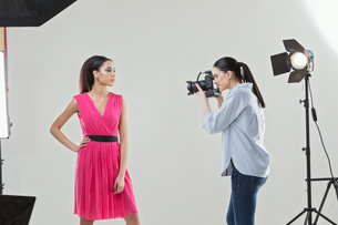Photographer photographing fashion model in white backdrop photography studio shootの写真素材 [FYI03576773]