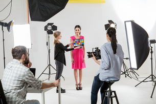 Photographer checking colour setting in white backdrop photography studio shootの写真素材 [FYI03576774]