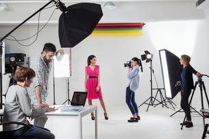 Photographer photographing fashion model in white backdrop photography studio shootの写真素材 [FYI03576775]