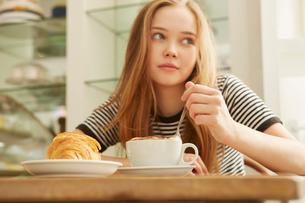 Girl in cafe stirring coffeeの写真素材 [FYI03576785]