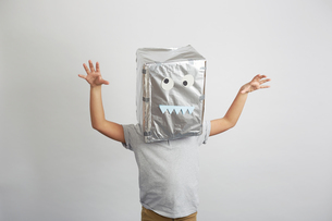 Portrait of boy with silver box on head, funny face on boxの写真素材 [FYI03576796]